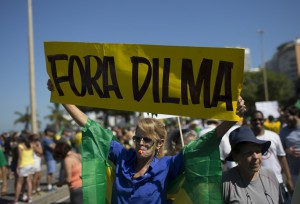 "A woman holds up a sign that read in Portuguese ""Dilma Out"" during an anti-government protest demanding the impeachment of Brazil's President Dilma Rousseff in Rio de Janeiro, Brazil, Sunday, Aug. 16, 2015. Demonstrators are taking to the streets across Brazil for a day of nationwide anti-government protests. President Rousseff's second term in office has been shaken by a snowballing corruption scandal involving politicians from her Workers' Party, as well as a spluttering economy, spiraling currency and rising inflation, making her popularity ratings fall to historic lows. (AP Photo/Leo Correa)"